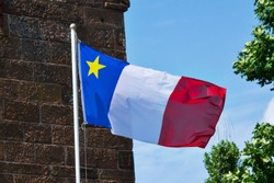 The Acadian flag on a mast in Prince Edward Island