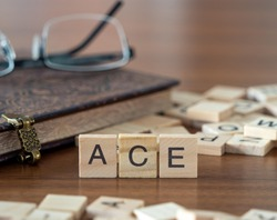 the acronym ace for Adverse Childhood Experiences concept represented by wooden letter tiles on a wooden table with glasses and a book