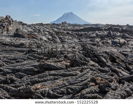 The active lava flow from a new crater on the slopes of volcanoes Tolbachic, on background volcano Bolshaya Udina - Kamchatka, Russia
