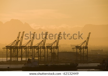 The active shipping harbor of Cape Town, South Africa seen from the neighborhood of De Waterkant at sunrise.