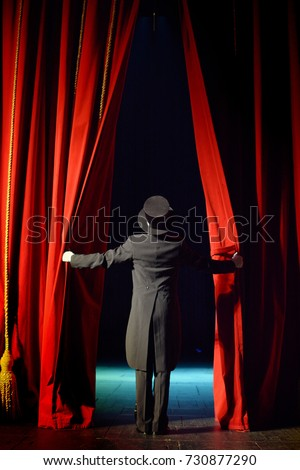 the actor opens a theater curtain