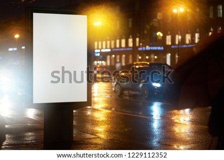 the ad billboard Billboard Ad Design, shines in the night city. mockup with a white field for advertising. rainy evening, wet weather and road #1229112352