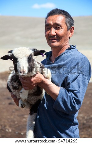 The adult man the shepherd carries on hands of a small lamb