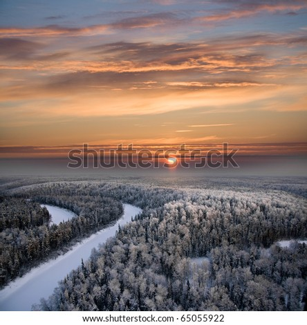 The Aerial view of snow-covered forest in time of sunny winter evening.