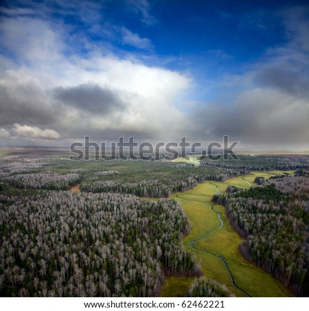 The Aerial view overhand of autumn forest and snow clouds.