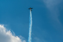 The aerobatic plane with smoke track in the sky