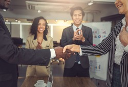 The african american businessman shaking hand with business woman after getting a good deal of mutual agreement in new project. All the parties feeling happy with this deal and agreement.