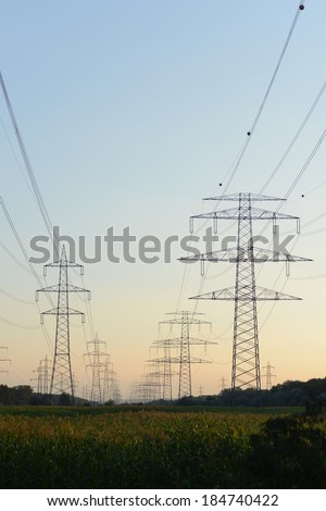 The afterglow of the transmission tower high voltage electrical network,electricity poles.