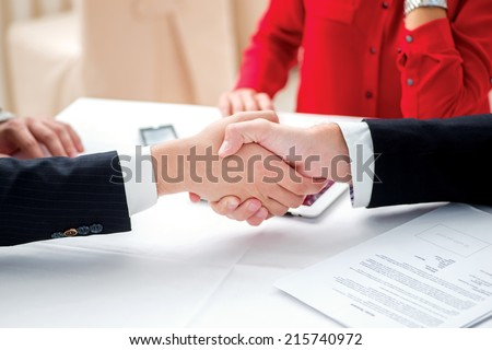 The agreement was signed. Three successful and confident businesspeople shake hands. Businesspeople in formal attire sitting in an office at a desk close-up view of hands