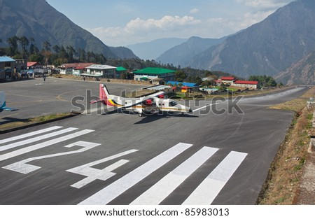 The aircraft on the runway of the airport Lukla - Nepal, Himalayas - stock photo