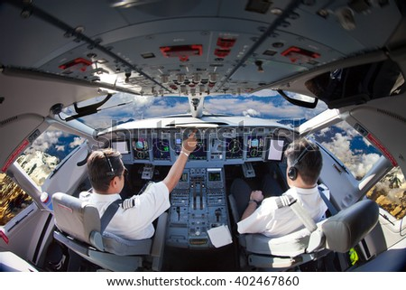 The Aircraft pilots at work. Plane is flying over the mountains. View from the cockpit.  #402467860