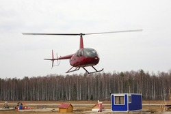 The aircraft - the red small helicopter makes flight at low height.
