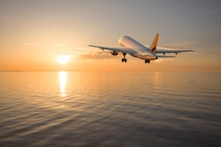 The airplane climbs, flying over the sea towards the sun at sunset