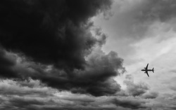The airplane fly in to gray clouds just before storm