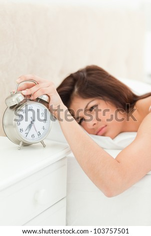 The alarm clock which is showing the time is being silenced by the woman's hand who is beside it lying on her bed while fully awake.