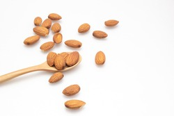 The almonds are in a brown wooden spoon and several seeds around which are on a white background.