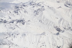 The almost abstract view of snowy peaks of the Caucasus Mountains in Georgia, Europe, on sunny day. Aerial view. Mighty tops of the mountains are completely covered with fresh snow. Winter background.