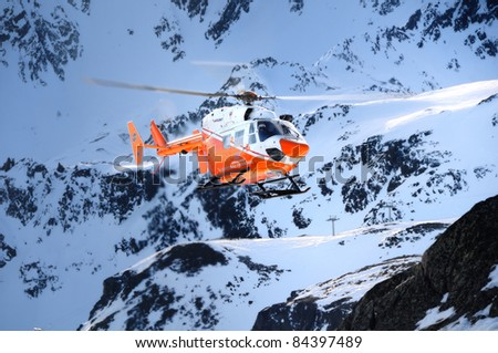 """THE ALPS, ITALY - CIRCA FEB 2011:A Pelikan Rescue Helicopter of """"Elisoccorso Provinciale Sudtirolo"""" flies through the mountains in South Tirol in search of avalanche victims CIRCA FEB 2011 in The Alps - stock photo"""