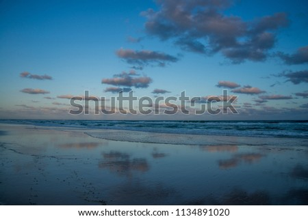 The amazing colorful sunset on Ballina beach in cloudy summer day. The reflection on natural water mirror. Best vocation and outdoor activity in New South Wales in Australia.