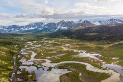 The amazing wilderness of northern Canada in summer time with snow capped peaks, winding rivers below by drone, aerial view.