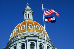 The American and Colorado flags at the Colorado state capitol building in Denver.