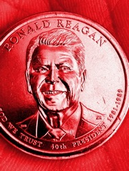 The American coin lies in the palm. 1 dollar coin with the portrait of President Ronald Reagan. Close-up. Vertical illustration is tinted red. US political news. Republican Party. Macro