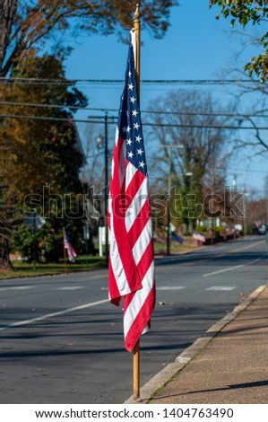 The American Flag displayed roadside during a Veterans Day Parade #1404763490