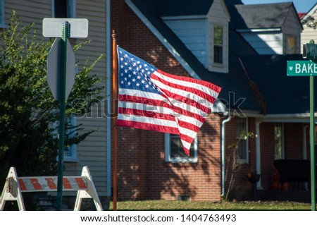 The American Flag displayed roadside during a Veterans Day Parade #1404763493