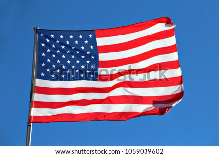 The American flag, known as the star spangled banner, on a flagpole. Flag of the United States of America.