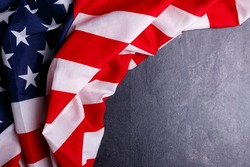 The American flag lies in an arc on a gray background