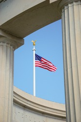 The American flag viewed through the  columns of the peristyle in St. Mihiel American Cemetery and Memorial