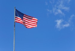 The American flag waves in the wind against a blue sky.