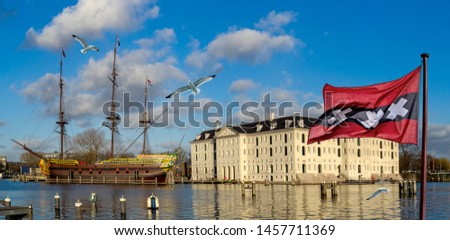 The Amsterdam marine skyline with city flag, seagulls and modern replica of a historic three-masted sail clipper moored near the Maritime Museum, the Netherlands tourist landmarks. Stockfoto ©