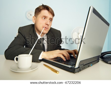 The amusing businessman drinks coffee through a straw without distracting from work in the Internet