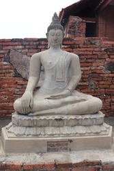 The ancient Buddha statue,white Buddha statue,it is Thai art and more than 200 years old but in perfect condition,The background is old bricks, made of cement,Buddhists respect and wish for fortune.