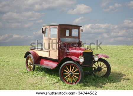 The ancient car  of red color with wooden wheels
