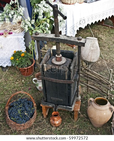 The ancient device for squeezing juice from grapes to make wine at home, decanters, a basket of grapes - stock photo