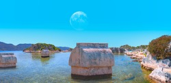 The ancient Lycian sarcophagus in water with full moon - Simena village, Kekova, Turkey.
