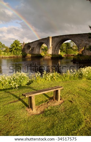 The ancient medieval bridge at Stirling captured in the soft light of early morning with a rainbow in the background.