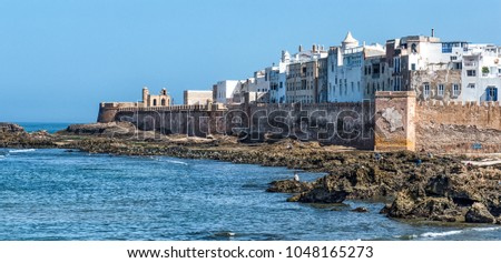 The ancient ramparts of the coastal town of Essaouira, Morocco. The fortress walls surround the old medina of Essaouira. The town is famous for its blue colours, especially the blue fishing boats. - Shutterstock ID 1048165273