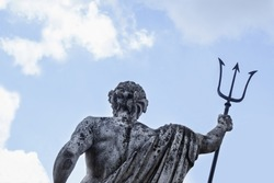 The ancient statue of god of seas and oceans Neptune (Poseidon) against blue sky