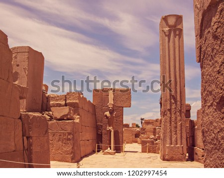 The ancient statue of the king (God or Pharaoh) and the stone column are surrounded by walls with hieroglyphs and ancient Egyptian symbols. Objects are located in Karnak Temple in Luxor, Egypt #1202997454