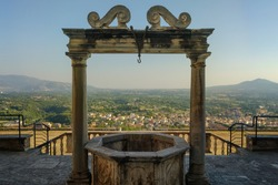 The ancient water well in front of Palazzo Colonna Barberini with panorama with hills near Rome on the background, Palestrina, Italy
