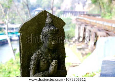 The ancient weathered buddha sculpture and the background of the famous Death railway in Kanchanaburi, Thailand.