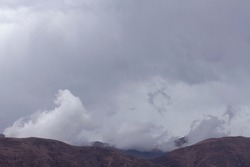 The Andes mountains early in the morning. View of the brown mountains, and mountain peak under a cloudy sky.