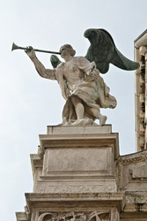 The angel blew his trumpet, antique decorations statue on the facade of a palace in Venice, Italy. Bible plot of the Revelation story about The Seven Angels with the trumpets