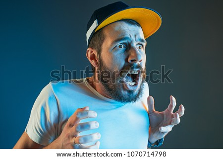 The anger and screaming man. Hate, rage. Crying emotional angry man in colorful bright lights at studio background. Emotional face. Fan human emotions, facial expression concept. #1070714798