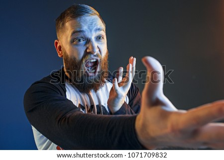 The anger and screaming man. Hate, rage. Crying emotional angry man in colorful bright lights at studio background. Emotional face. Fan human emotions, facial expression concept. #1071709832