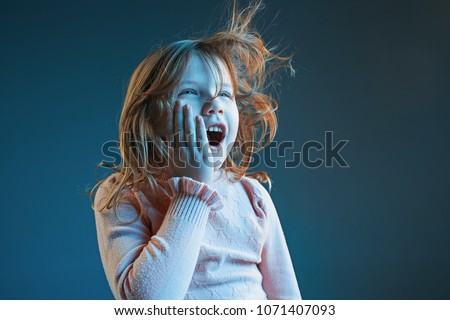 The anger and surprised teen girl. Hate, rage. Crying emotional angry teenager in colorful bright lights at studio background. Emotional face. Sport fan human emotions, facial expression concept. #1071407093