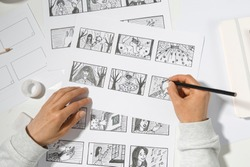The animator artist draws in pencil a storyboard for the cartoon. Pre-production for the video film. The designer creates sketches for the comics.